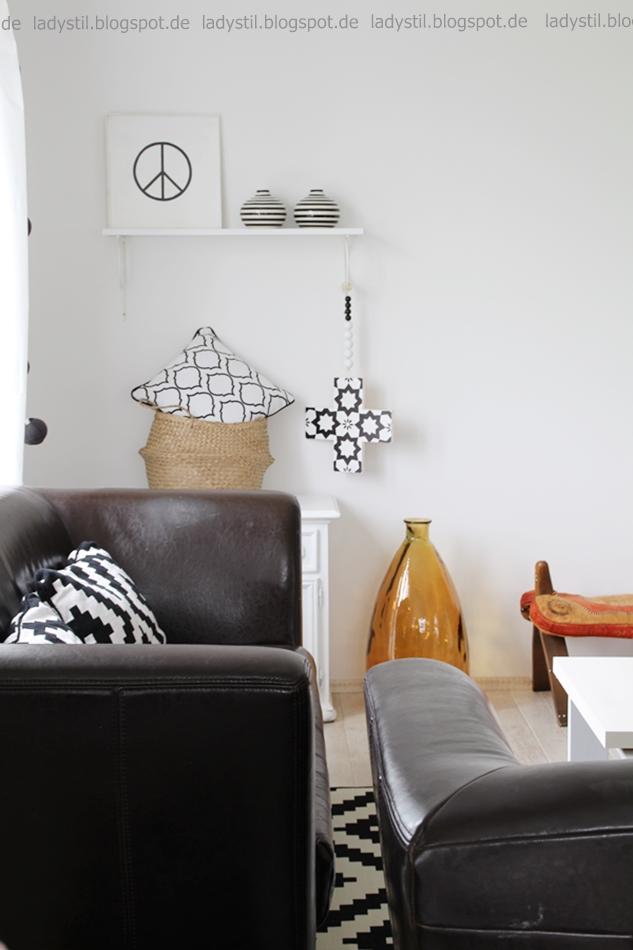 Blick auf zwei Sofas von hinten mit Sicht auf ein Regal mit schwarzweißen Accessoires marokkanischem Hocker und brauner Vase
