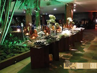 mesa de vidro com pés de madeira, velas âmbar, caixas forradas, arranjo floral, casamento