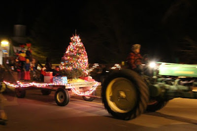 tractor pulling a Christmas tree on a hay wagon