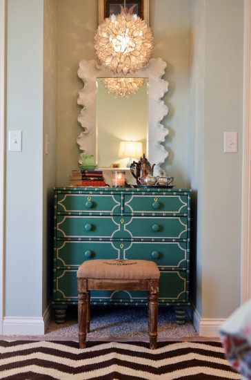 Beautiful girl's bedroom with chevron rug, aqua and coral color scheme, teal dresser, white scalloped mirror, and round lotus capiz shell pendant light