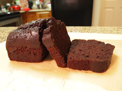 a small loaf of chocolate cake with two slices on the right; one fell and is lying face up
