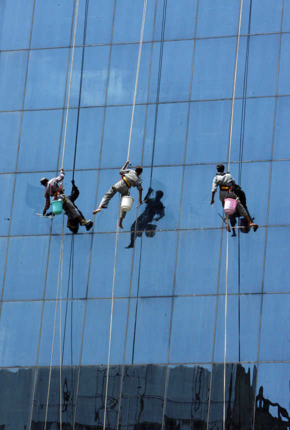 window cleaners work on a high rising building in new delhi. Resume Example. Resume CV Cover Letter