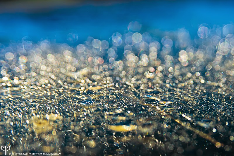 An artistic bokeh photograph by Tom Cunningham of water droplets on top of a colourful parking meter in St Kilda Melbourne