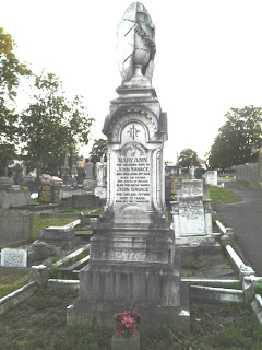 A tall pillar style gravestone, square in section and made of white stone.  It rises from a tierd base to a square column with writing insised in an arched panel.  Upwards the column tapers to a plinth which is surmounted by a draped vase.