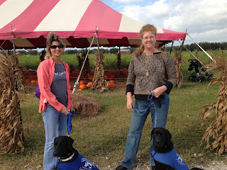 Melisa and Cheryl stand with Bo and Coach in front of the pumpkin patch.