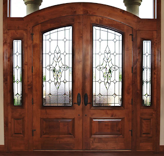 Photo of burgundy double doors in the entry way of a home with beveled glass