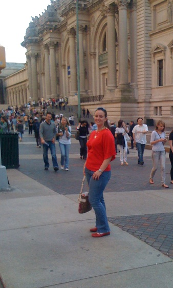 White girl with dark hair wearing jeans and red sweater stands in front of the Metropolitan Museum of Art. Crowds of people walk in the background.
