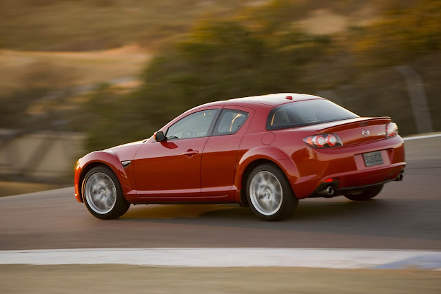 Rear 3/4 view of 2011 Mazda RX-8 driving