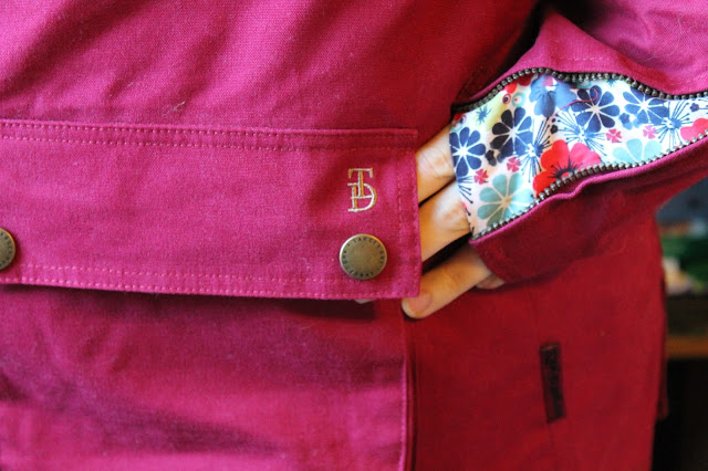 close up of target dry kendal waterproof coat in rumba with floral detail on arm