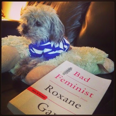 Murchie lays on a fuzzy white pillow. He wears a blue and white striped t-shirt. In front and slightly to one side of him is a trade paperback copy of Bad Feminist. Its cover is entirely white with the title in pink and the author's name, Roxane Gay, in black.