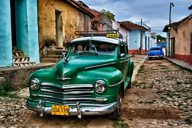 Old american green car taxi and blue taxi in Cuba
