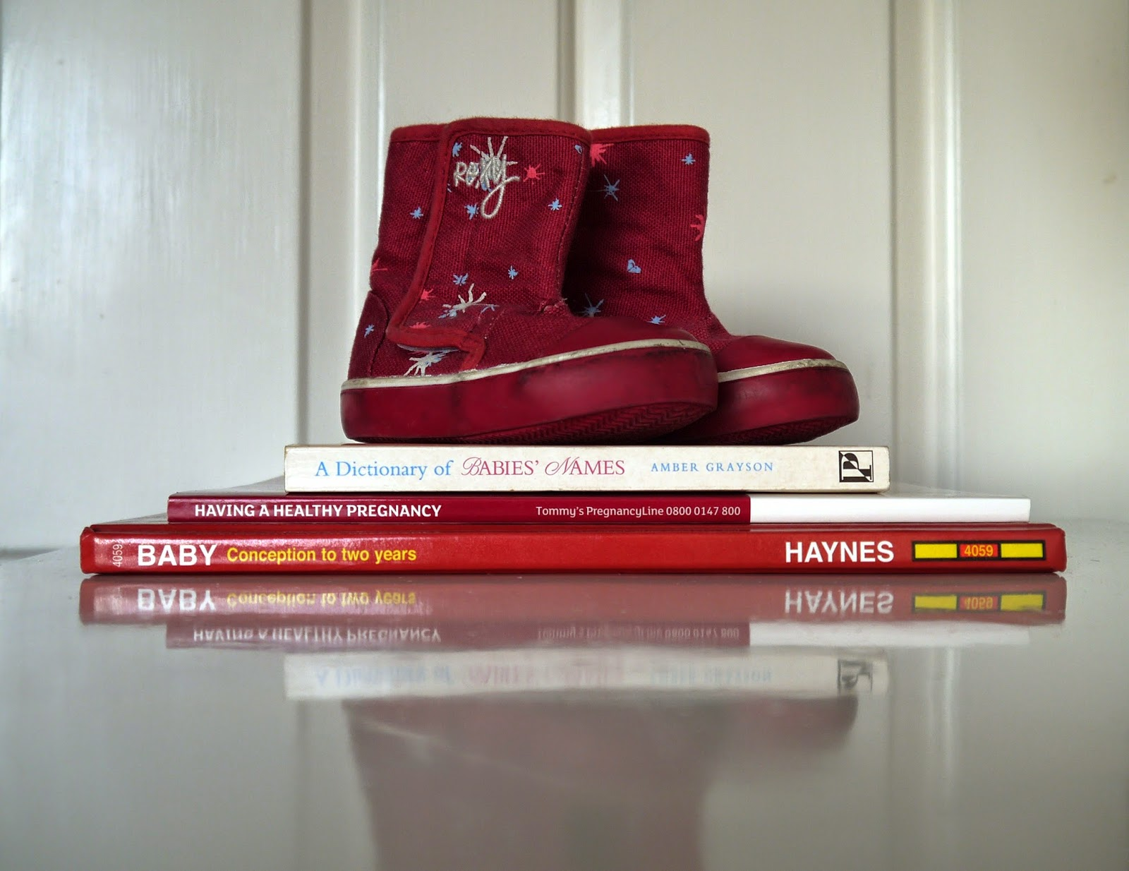 Pregnancy and parenting books and empty shoes