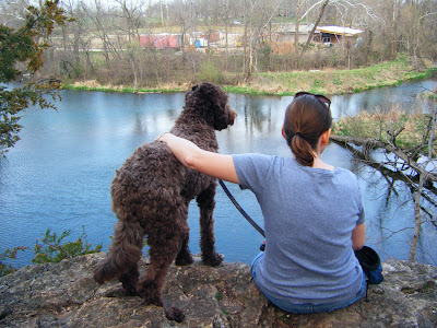 Back view of Beth & Alfie at the edge of a rocky cliff looking out over a pond; I'm sitting with my legs hanging over and have my arm over Alfie, who's standing next to me