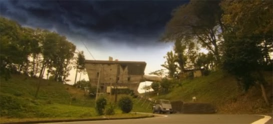 The professor's car drives up a winding road to a oddly shaped building that serves as his lab, under a sky heavy with dark clouds.