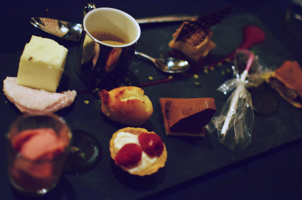 picture of a Café gourmand in a restaurant in lille france. it contains strawberry mousse, cranberry tart, mousse au chocolat, madeleine and a coffee