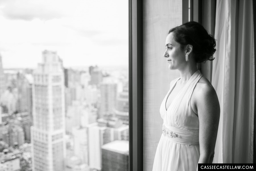 Side profile of bride wearing Nicole Miller wedding dress and vintage diamond chandelier earrings looking out window at Central Park. NYC Lifestyle wedding photography by Cassie Castellaw. www.cassiecastellaw.com