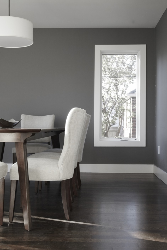 Picture of dining room with dark grey walls and dark wooden floor but light grey chairs