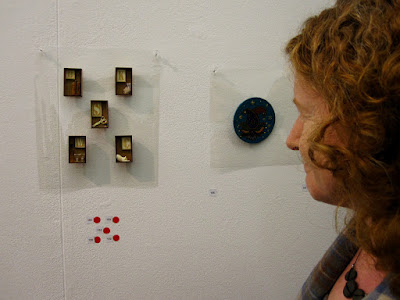 A woman admiring five sold brooches on display in a gallery.