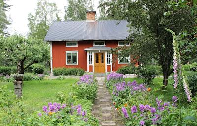 Huset är målat med falu rödfärg. Perennrabatter leder mot farstukvisten.