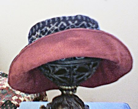 Brimmed hat of Guatemalan cotton in shades of navy, white and dark burgundy. In the front of the hat, the brim is folded up to display a lining of burgundy flannel