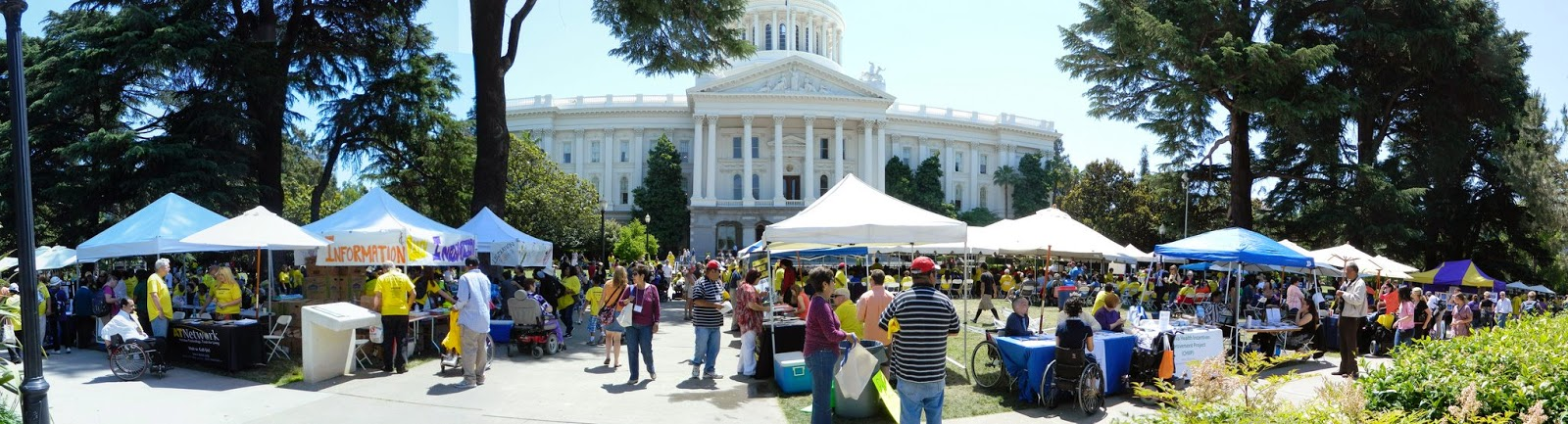 picture of the capitol with a dozen resource booths with tents and lots of people milling around them