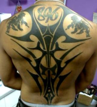 Black ink tribal back tattoo with inscription 8%