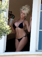 Courtney Stodden standint at her window in a tiny bikini,