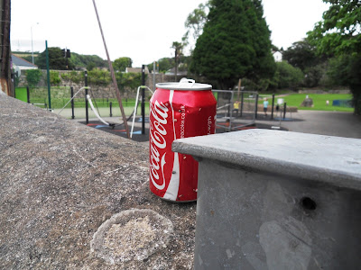 Coca-Cola tin by a park and playground