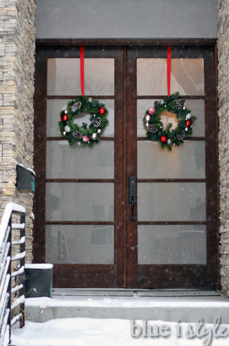 ... The Green Wreaths With Flocked Pinecones And Shiny Ornaments Look Very  Festive Hanging From Red Ribbons On The Outside Of Our Front Doors.