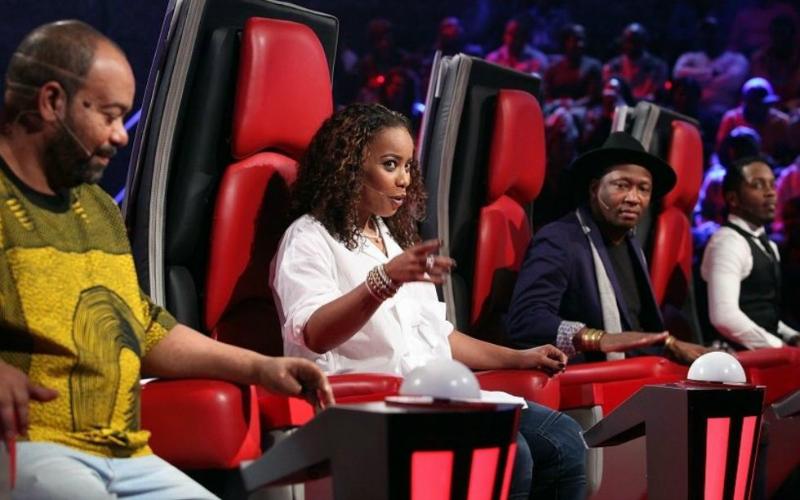 Na imagem de capa: Foto do The Voice angola, mostrando as cadeiras vermelhas dos coaches de lado, todos eles negros, em destaque a única mulher que está apontando para o palco e olhando com uma expressão divertida.