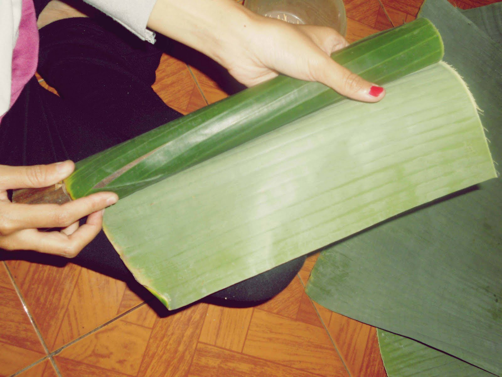 Ambil daun pisang, kemudian gulung dengan cetakan bambu