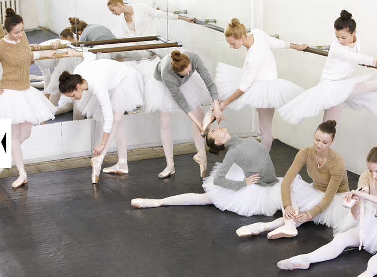 Ballerinas stretching at the barre in the studio, dancers, ballet, pointe shoes