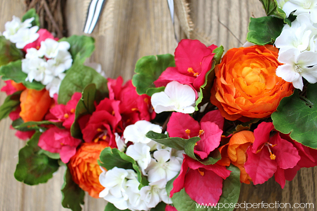 Ranunculus, geraniums and bright pink flowers are the perfect basis for this Bright Blooms & Bold Stripes Summer Wreath.