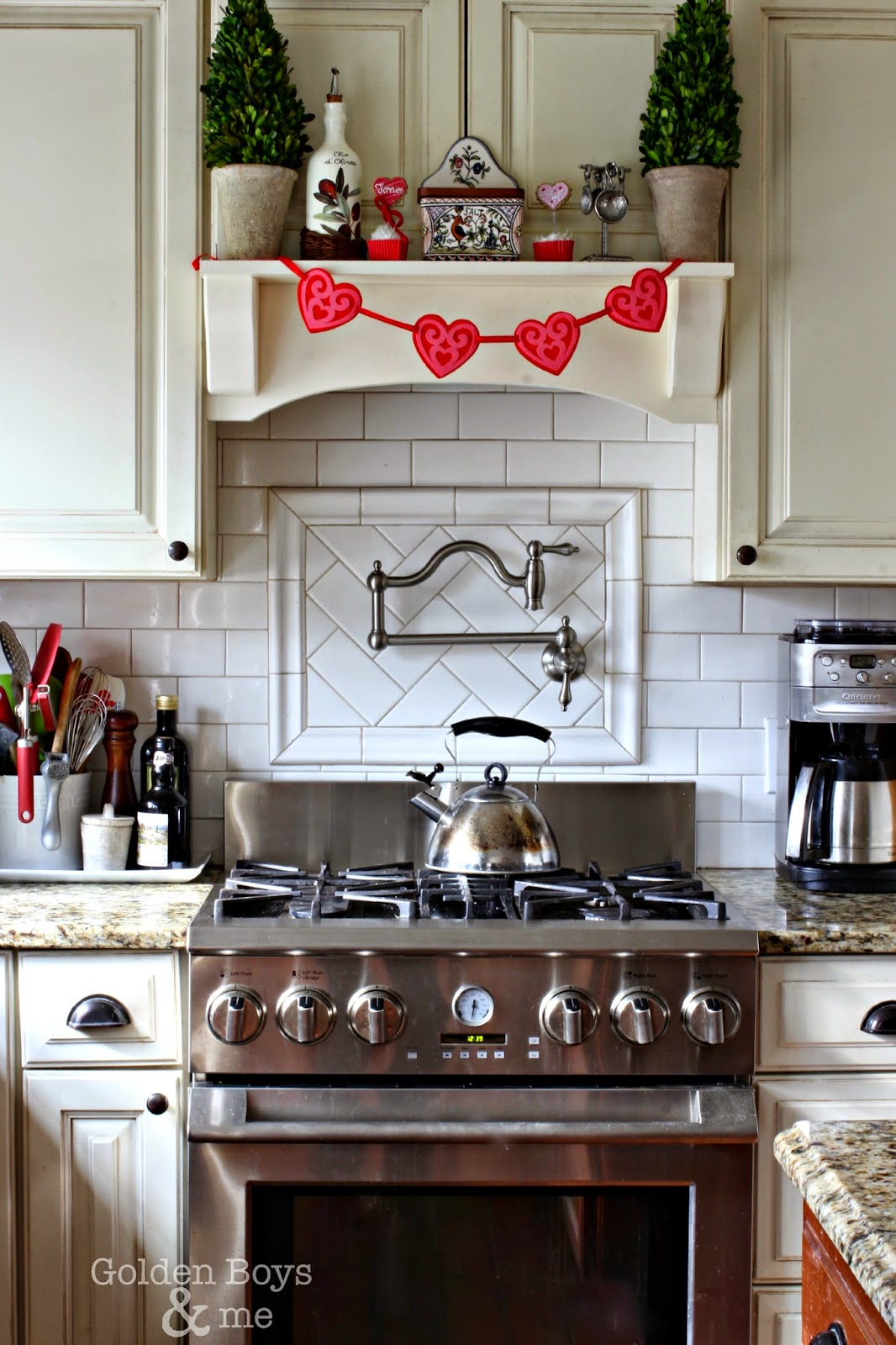 Target dollar spot heart garland on range hood mantel shelf-www.goldenboysandme.com
