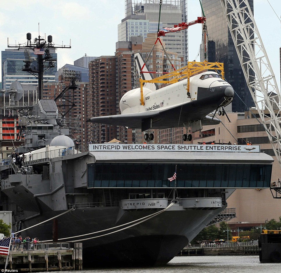 the space shuttle enterprise is lowered onto the flight deck of the uss intrepid which floats on the hudson river in new york city