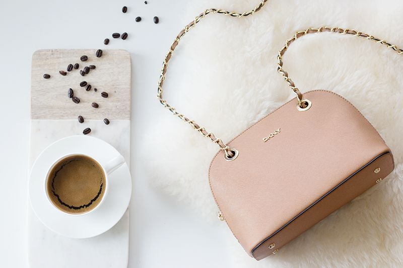 Coffee flatlay with DKNY crossbody bag