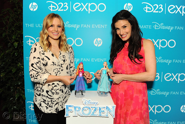 "Kristen Bell and Idina Menzel, voice talent of Anna and Elsa in the upcoming Walt Disney Animation Studios film ""Frozen,"" pose with Mattel's Anna and Elsa Frozen Feature Fashion Dolls during The D23 Expo – The Ultimate Disney Fan Event"