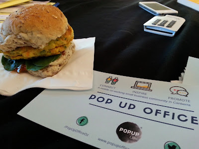 A vegeburger on a napkin next to a flier for The Pop Up Office.