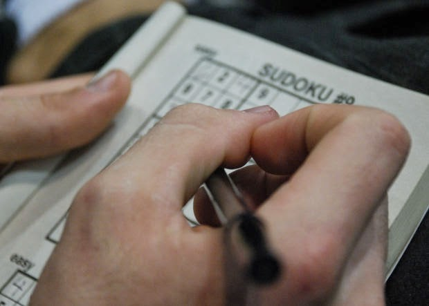closeup of hand doing a sudoku number puzzle