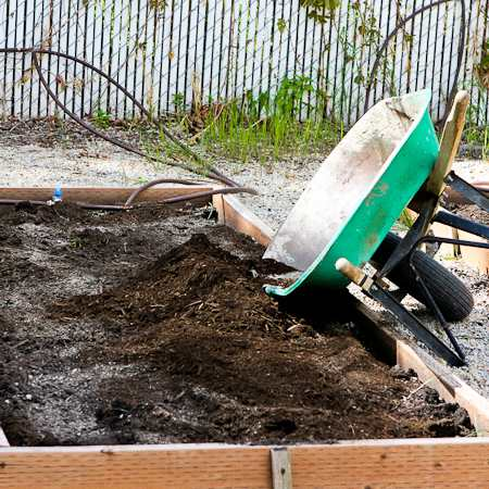 raised garden beds with organic material being added
