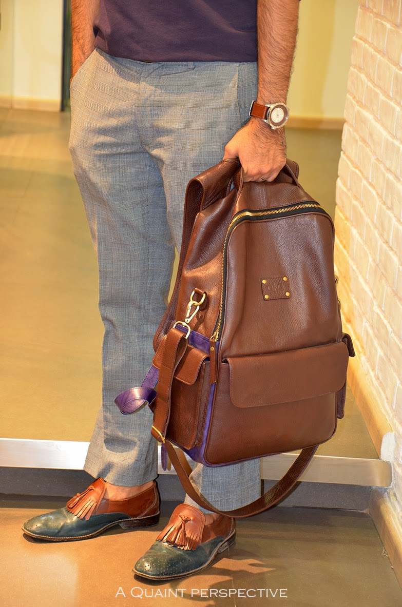 There is a certain attraction in the play of textures, the updated color blocking in the designs, both from the label A.K.A Bespoke, that he is a part of. The contrasts, the green+brown in the shoes and the purple+brown for the backpack are subtle and striking at the same time.