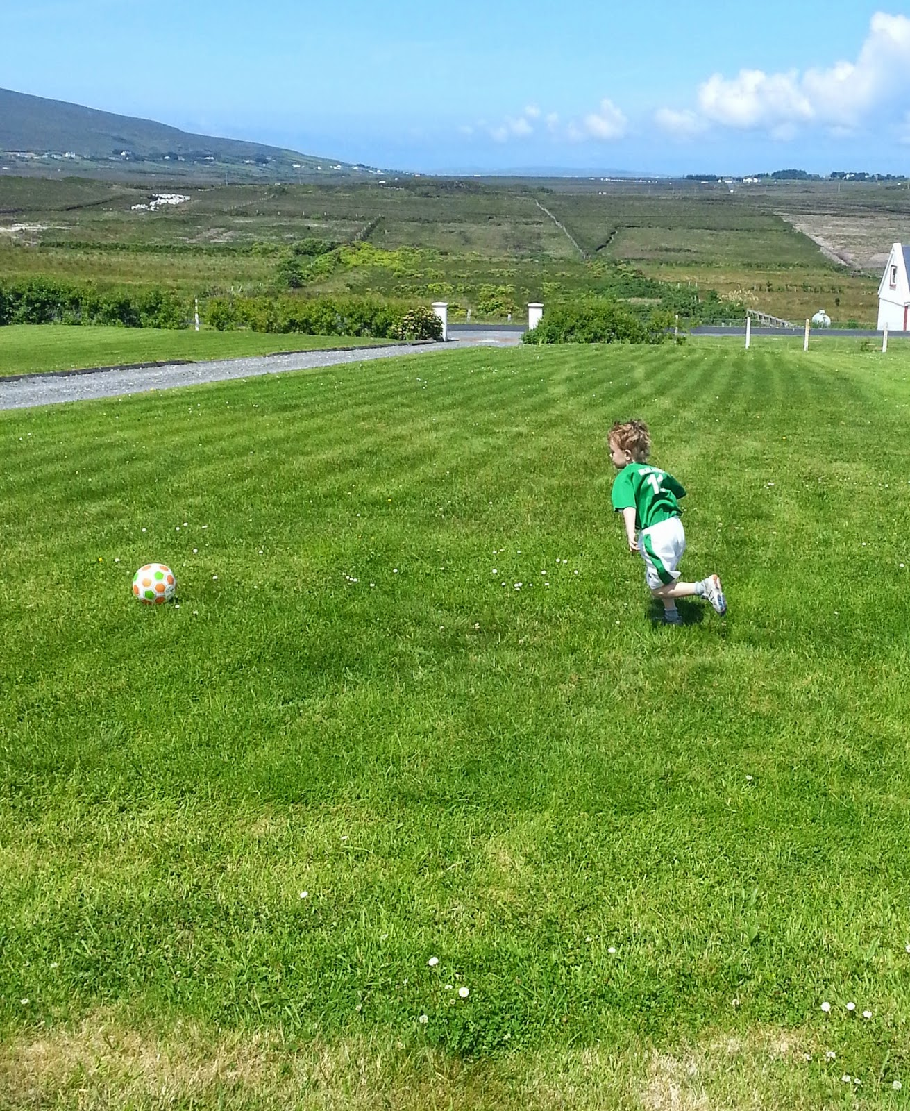 young boy in Ireland kit kicking Ireland ball on beautiful green lawn, blue sky in the background with candyfloss clouds