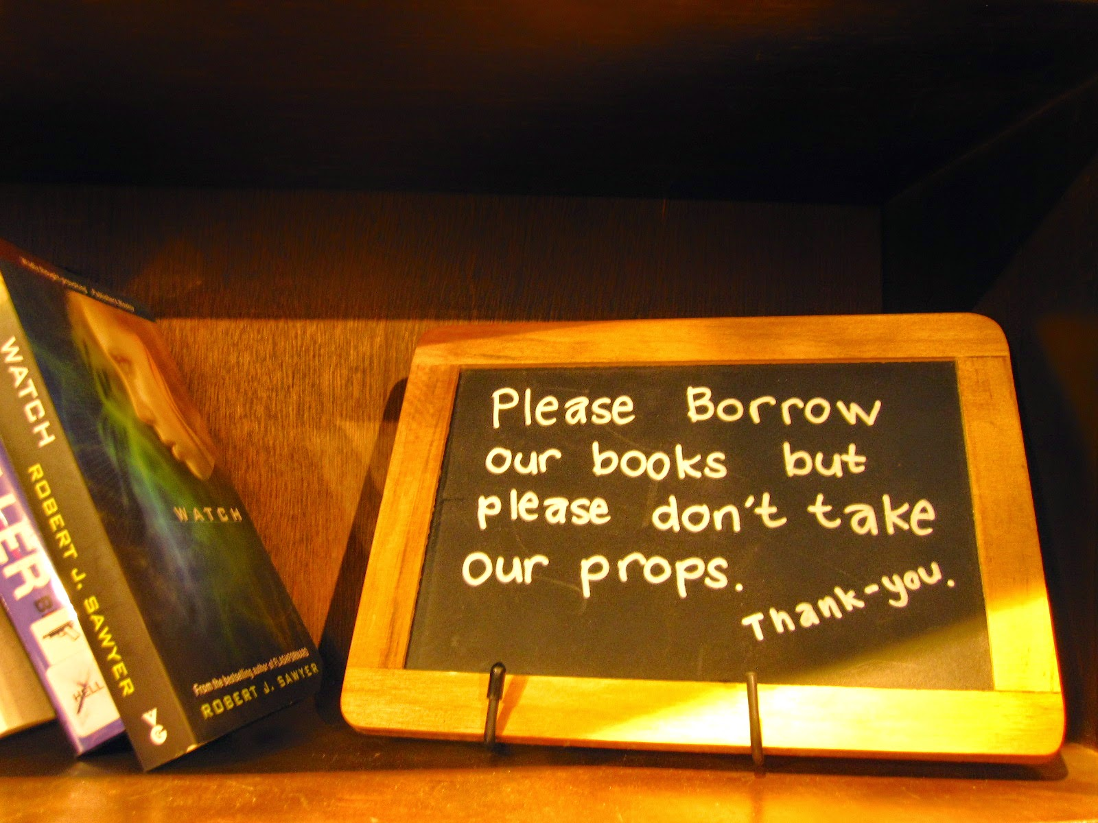 Blackboard sign on a shelf of books at The Little Library in Melbourne Central: 'Please borrow our books, but please don't take our props. Thank you.'