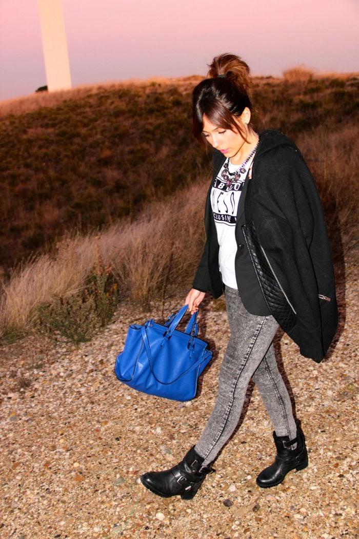 botas moteras, pantalon gris, bolso azul, abrigo negro,