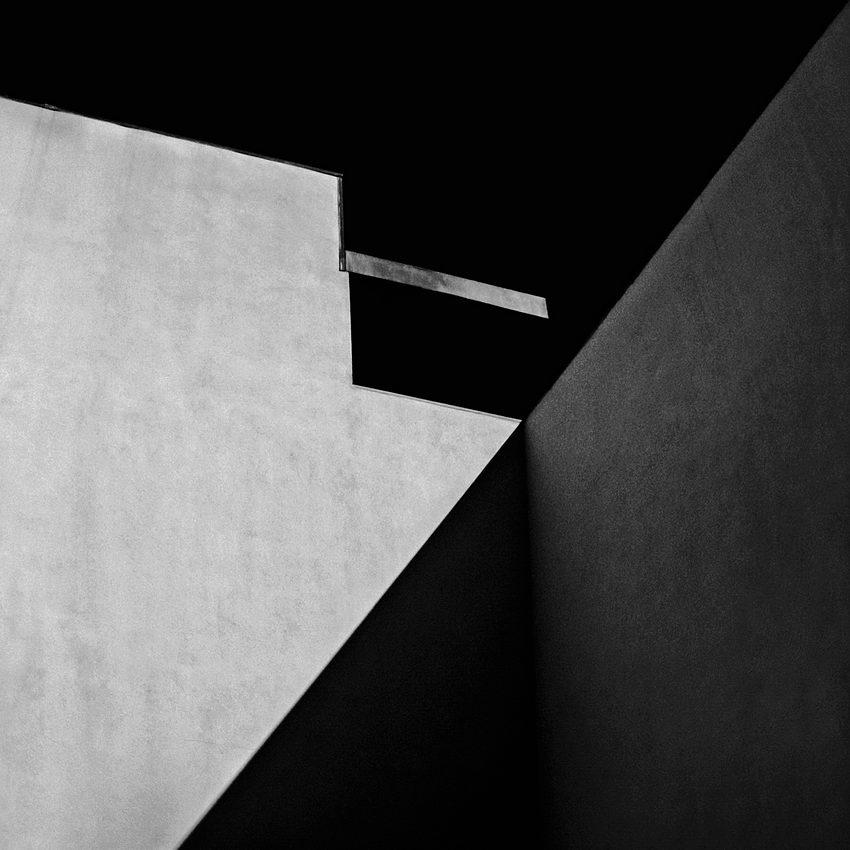 Foto a preto e branco num canto de duas paredes com o sol numa posição que originou alinhamento da sombra com o topo da parede