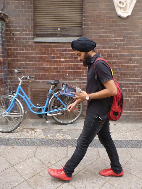 Ein indisch aussehender junger Mann, schwarz gekleidet, mit Turban und rotem Rucksack und Schuhen, liest im Gehen einen Indien-Reiseführer