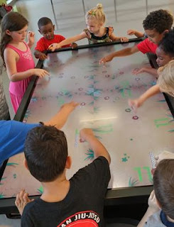 Picture of children interacting on a Clear Touch multi-touch table and NUITEQ Snowflake MultiTeach Software.