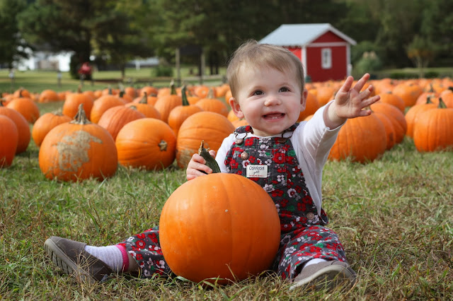 Madeline waving with her pumpkin