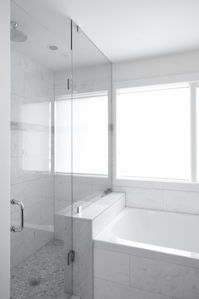 Picture of glassy shower cabin by the white bathtub in the bathroom
