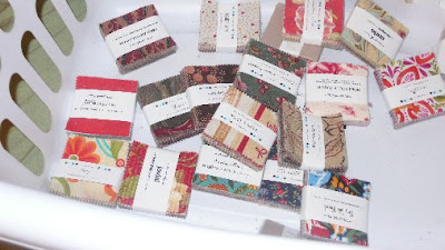 a photo of at least a dozen little parcels of various prints, including ones of buttons, shirts, and severl solids.